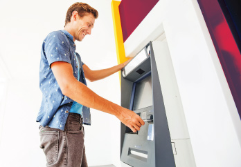 Young man smiling and using an ATM to withdraw cash