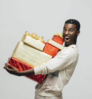 young male smiling and holding a stack of wrapped christmas gifts in his arms
